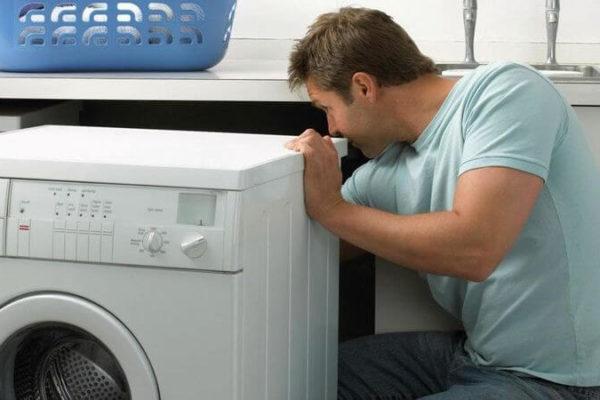 Электрик подключает стиральную машину